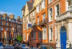 Londen, het UK Woonaria van Kensington en Chelsea Cadoganpoort met rij van periodieke gebouwen Luxesteun Stock Foto's