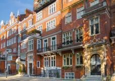 Londen, het UK Woonaria van Kensington en Chelsea Cadoganpoort met rij van periodieke gebouwen Luxesteun Stock Foto