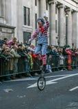 Londen, het Verenigd Koninkrijk - Januari 1, 2007: De mens in clownkostuum berijdt unicycle, en golven aan het toejuichen van men stock foto