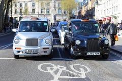 Londen, het VERENIGD KONINKRIJK, 09 04 2016 Twee Londonian de taxibestuurder spreekt aan elkaar, die bij een rood licht wachten Stock Foto