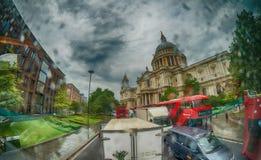 LONDEN - JUNI 2015: Rode bussen dichtbij St Paul Cathedral op regenachtig royalty-vrije stock fotografie