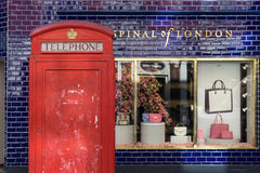 Londen - Maart 30: Iconische telefooncel voor winkel met blauwe tegelmuur op 30 Maart, 2017 Stock Afbeeldingen