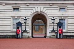 LONDEN - MEI 17: De Britse Koninklijke wachten bewaken de ingang aan Buckingham Palace op 17 Mei, 2013 Stock Foto's