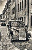 LONDEN - MEI 2013: Zwarte cabine langs oude stadsstraat Attra van Londen Stock Foto's