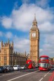 Londen met rode bussen tegen Big Ben in Engeland, het UK stock afbeeldingen