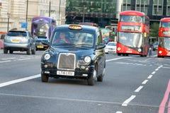 LONDEN - SEPTEMBER 25, 2016: De rode bussen en de zwarte cabine versnellen binnen Stock Fotografie
