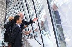 Londen, Twee bedrijfsmensen die op de horizon van Londen van vloer 32 van het bekijken van zaal letten Stock Afbeeldingen