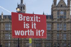 Red protest sign with text Brexit is it worth it in the front of the houses of. Londen - United Kingdom, October 11, 2018: Red protest sign with text Brexit is stock photography