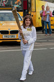 London 2012 Olympic Torch Relay. An unidentified torch bearer carrying the Olympic Torch through Penrith town centre in Cumbria, England ahead of the 2012 London Stock Photos