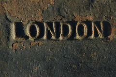London. The name of the UK capital, LONDON, raised in metal on metal with rust and chipped black paint Royalty Free Stock Images