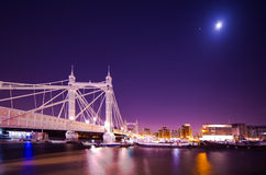 London. Albert Bridge River Thames by night moon Royalty Free Stock Photos