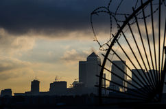 London behind bars. Canary wharf skyline behind barbed wire Royalty Free Stock Photo