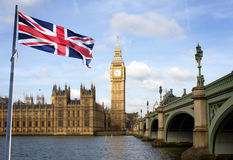 London Big Ben and Westminster bridge and british flag. Against blue sky stock image