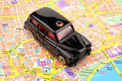London Black Cab. A black cab taxi, on a map of London city royalty free stock images
