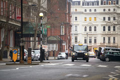 London black cab. Famous London black cab in residential road in early evening. There are cars parked on the sides, and traditionally British residential royalty free stock photos