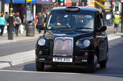 London black cab in Oxford street London UK. LONDON - MAY 14 2015:London black cab. The driver is expected to know over 25,000 roads and 20,000 landmarks and royalty free stock images