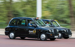 London black cab taxis in motion. London, UK - April 25, 2017: Two London`s black Cab taxis in motion on the street Stock Images
