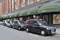 London black cabs Harrods department store. Taxi rank with London black cabs by Harrods department store in Knightsbridge royalty free stock photo