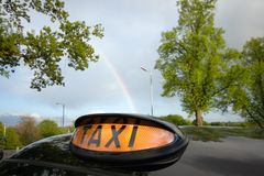 London Black Taxi Cab and Rainbow. London taxi for hire, with a rainbow in the background stock images