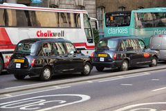 London black taxi following each other in front of the busses on the road. London street traffic with two black taxi cab and two big buses are moving along the stock photos