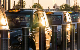 London black taxi rank. London, UK - 13 May 2015: A dusk scene of a row of familiar London black taxi cabs lined up at a taxi rank waiting for passengers in stock images