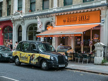 London black taxi with theatre advertisement parks outside Itali. London, England, August 23, 2015: A black London taxi decorated with theatre advertisement stock photos