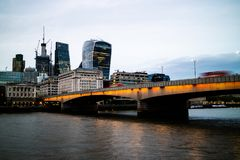 London Bridge with busses travelling across it in the evening stock photos