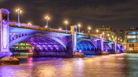 London bridge at Night. In Winter under cloudy sky with brautiful reflection on river Thames water and coloured light from street lanterns in a winter evenieng Stock Images