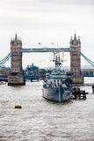 London Bridge. The London bridge over the river Thames, with a navy ship docked on the south bank stock images