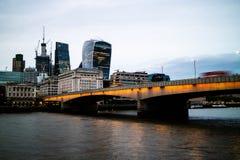London bro med bussar som reser över den i aftonen arkivfoton