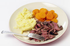 London broil meal with fork. London broil marinaded flank of beef steak grilled and sliced thinly, then served with mashed potato, boiled sliced carrots and Royalty Free Stock Image