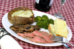 London Broil Steak Dinner. London broil steak, baked potato, semolina bread, mushrooms and broccoli cooked to perfection Stock Photography