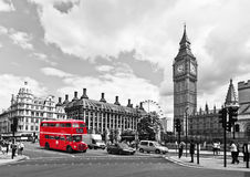London bus. With selective red color, on black and white London cityscape, with Big Ben and London Eye in the background Royalty Free Stock Images