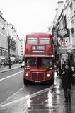 London Bus. Picks up passengers at a bus stop on a wet day Stock Photos