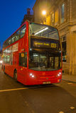 London bus at night. Red London bus driving down street at night, England Stock Photography