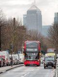 London-Bus und schwarzes Fahrerhaus an der Hauptverkehrszeit Canary Wharf-Hintergrund Lizenzfreies Stockbild
