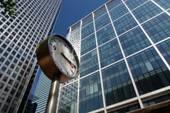 London Business Time. A chrome clock by the office blocks in London's business and financial district Royalty Free Stock Photography