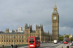 London buss som korsar den Westminster bron Arkivbild