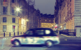 London cab. Blurred image of moving London taxi cab at dusk passing historic illuminated stone buildings stock photos