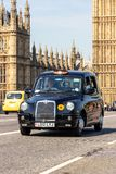 London cab taxi. LONDON - JUL 1, 2015: Black taxi cab driving over the Westminster Bridge near the Big Ben in London royalty free stock photo