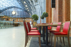 London cafe train station with red wood chairs and tables Royalty Free Stock Photography