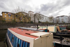 London Canal with boats overlooking flats. A small group of boats on a London canal with apartment buildings in the backgrounds during an overcast day Royalty Free Stock Photo