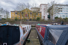 London Canal with boats overlooking flats. A small group of boats on a London canal with apartment buildings in the backgrounds during an overcast day Royalty Free Stock Photos