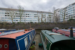 London Canal with boats overlooking flats. A small group of boats on a London canal with apartment buildings in the backgrounds during an overcast day Stock Photo