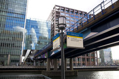 LONDON, CANARY WHARF UK -APRIL 13, 2014 - DLR bridge with train Modern glass architecture of Canary Wharf Stock Images