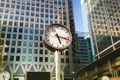 LONDON, CANARY WHARF UK - APRIL 13, 2014: - Modern glass architecture of Canary Wharf business aria and clocks on the main square Royalty Free Stock Photo