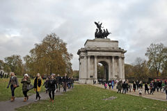 London Christmas shoppers. LONDON - NOVEMBER 30: Christmas shoppers walk under Wellington Arch en route to Hyde Parks Winter Wonderland attraction on November 30 Stock Images
