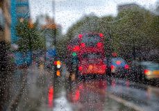 London city lights through window glass with rain drops. London traffic scene with Doubledecker bus seen through bus stop glass covered with rain drops - autumn Royalty Free Stock Photo