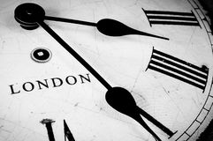 London Clock face. Black and white clock face with a cracked and weathered appearance displaying the time in London stock photo