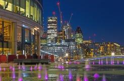 London - die Ansicht von mehr London-Flussufer über dem fountian zu den Wolkenkratzern in der Mitte an der Dämmerung Lizenzfreies Stockbild